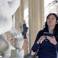 A visitor views a sculpture at the Louvre Museum in Paris with the help of the new audio guide, Thursday April 12, 2012. The famed Paris museum is going 3D visual with its electronic guides in a deal with Japan's Nintendo to provide game consoles to help visitors who navigate its labyrinthine halls by the millions each year. The guides, in seven languages, and accompanying headsets cost Euro5 ($6.50) on top of the museum's Euro10 standard admission price.