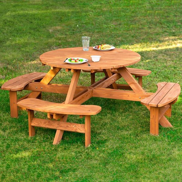 A round cedarwood picnic table with four attached benches