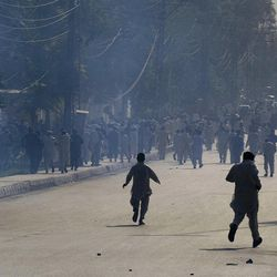 Angry protesters run for shelter after police fire tear gas to disperse them during a demonstration outside the U.S. consulate in Peshawar, Pakistan on Tuesday, Sept. 18, 2012. Hundreds of angry protesters broke through a barricade outside the U.S. Consulate in Peshawar, sparking clashes with police that left several wounded on both sides, police said.