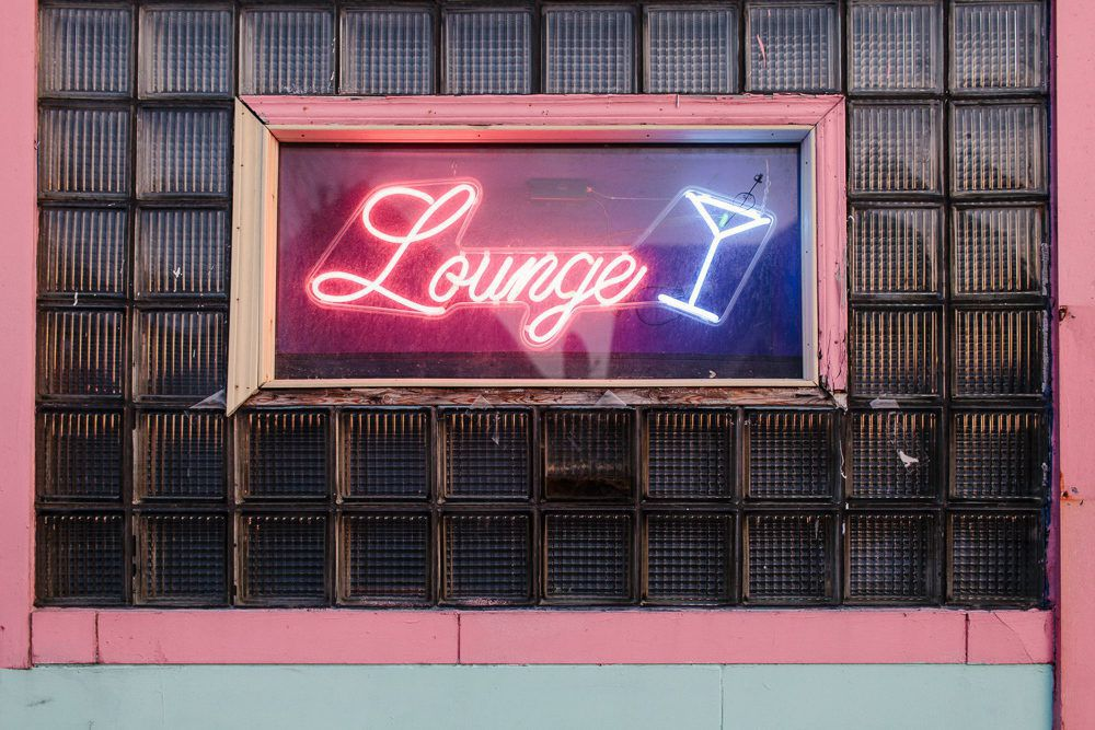 """A pink and blue fluorescent sign in a window at Painted Lady reads """"Lounge"""" with a martini glass."""