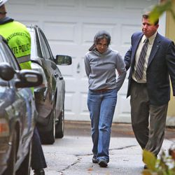 Annie Dookhan, center, is escorted to a cruiser outside her home in Franklin, Mass., Friday, Sept. 28, 2012. Dookhan is accused of faking drug results, forging signatures and mixing samples a state police lab. State police say Dookhan tested more than 60,000 drug samples involving 34,000 defendants during her nine years at the lab. Defense lawyers and prosecutors are scrambling to figure out how to deal with the fallout.