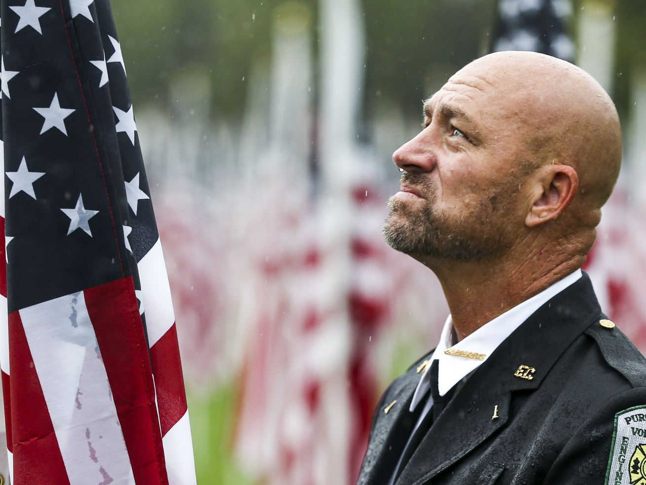 Phil Larson, a retired firefighter with the Round Hill Volunteer Fire Department in Washington, D.C., braves the rain at the 18th annual Healing Field in Sandy on Wednesday, Sept. 11, 2019, as he pays his respects to the men and women who lost their lives during the 9/11 attacks. Larson, a Sandy native, was one of the rescuers that responded to the attack on the Pentagon.