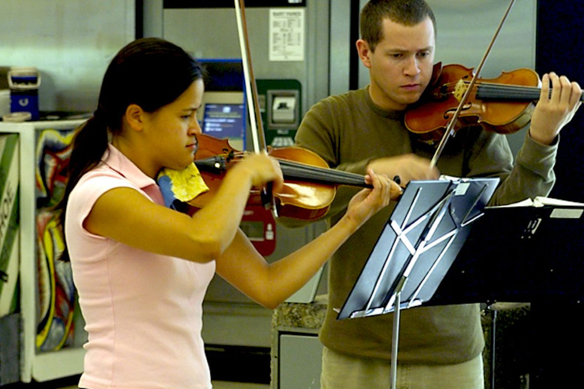 Two musicians playing violins in a BART Station.