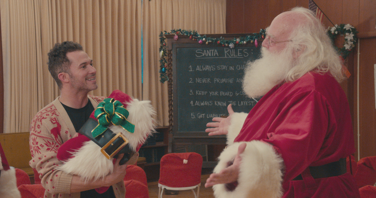 a man named justin stands next to santa claus