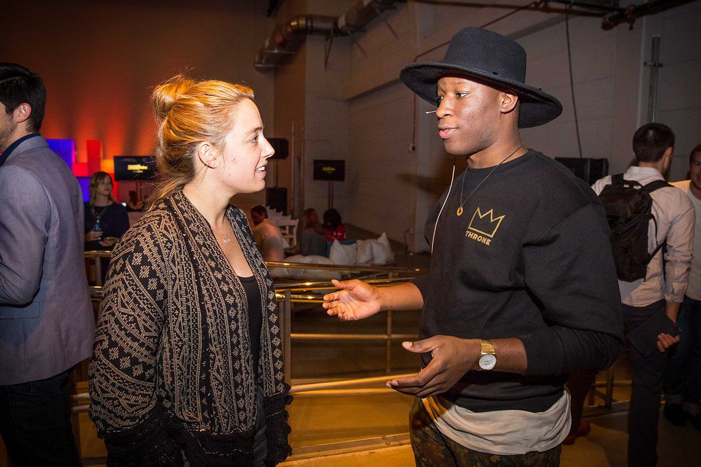 Throne CEO Emeka C. Anen, at right, talks about the company's peer-to-peer streetwear marketplace with a woman who attended the Smashd Labs Demo Day in Los Angeles.