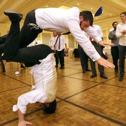 Chaim Levi Cohen jumps over Nochum Greenwald, who is doing a headstand, during Chaya Zippel and Rabbi Mendy Cohen's traditional Hasidic wedding at the Grand America Hotel in Salt Lake City on Monday, Sept. 12, 2016.