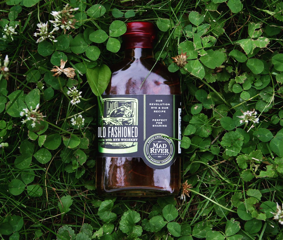 A glass bottle of a premixed Old Fashioned cocktail drink from Vermont's Mad River Distillers. The bottle lies on top of grass and clover.