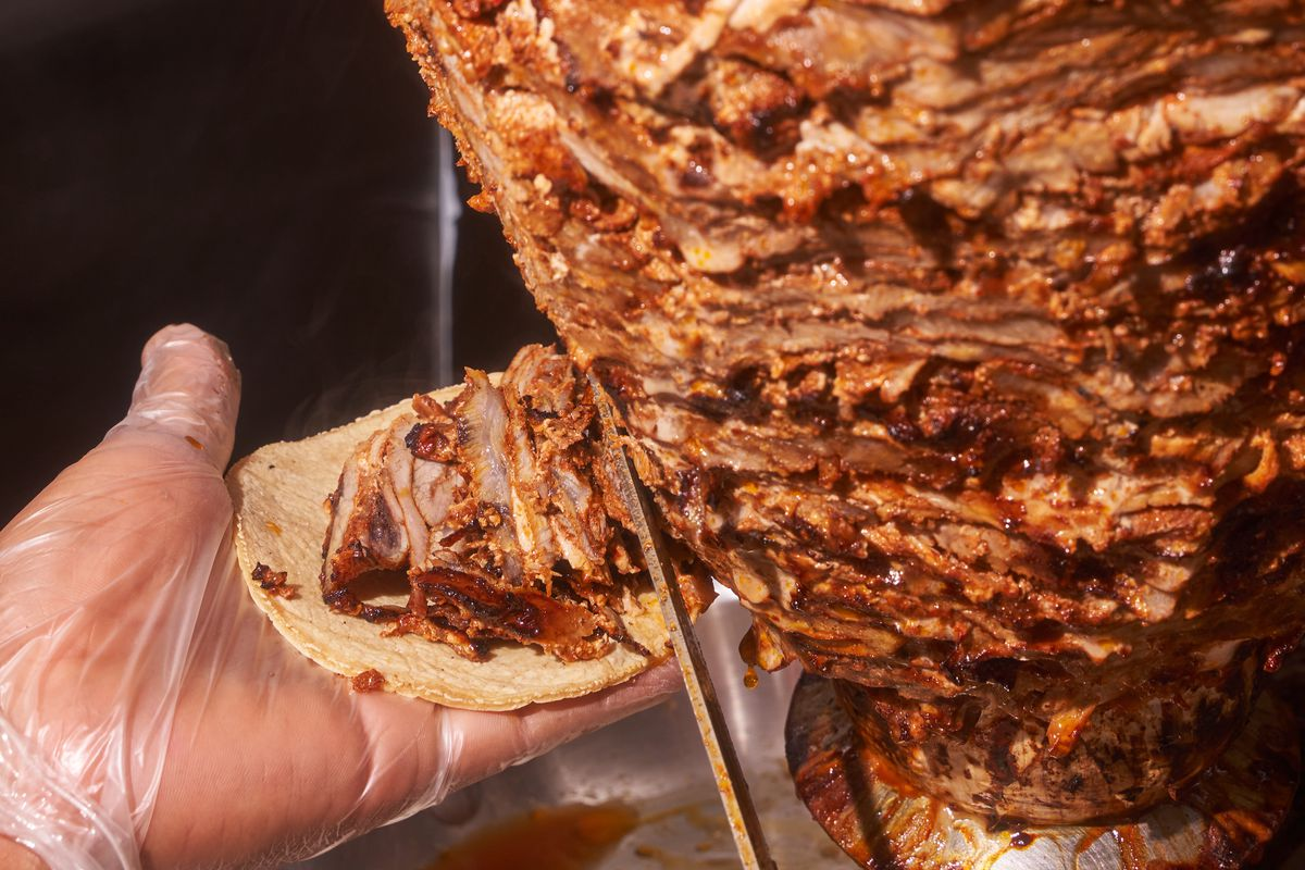 A knife cuts thin al pastor meat from the spit, which is caught by a gloved hand holding a tortilla