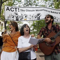 Krista Bowers, left, Joan Gregory and Miles Biddulph sing as supporters of Tim DeChristopher meet across the street from the federal courthouse in Salt Lake City, Tuesday, July 26, 2011.
