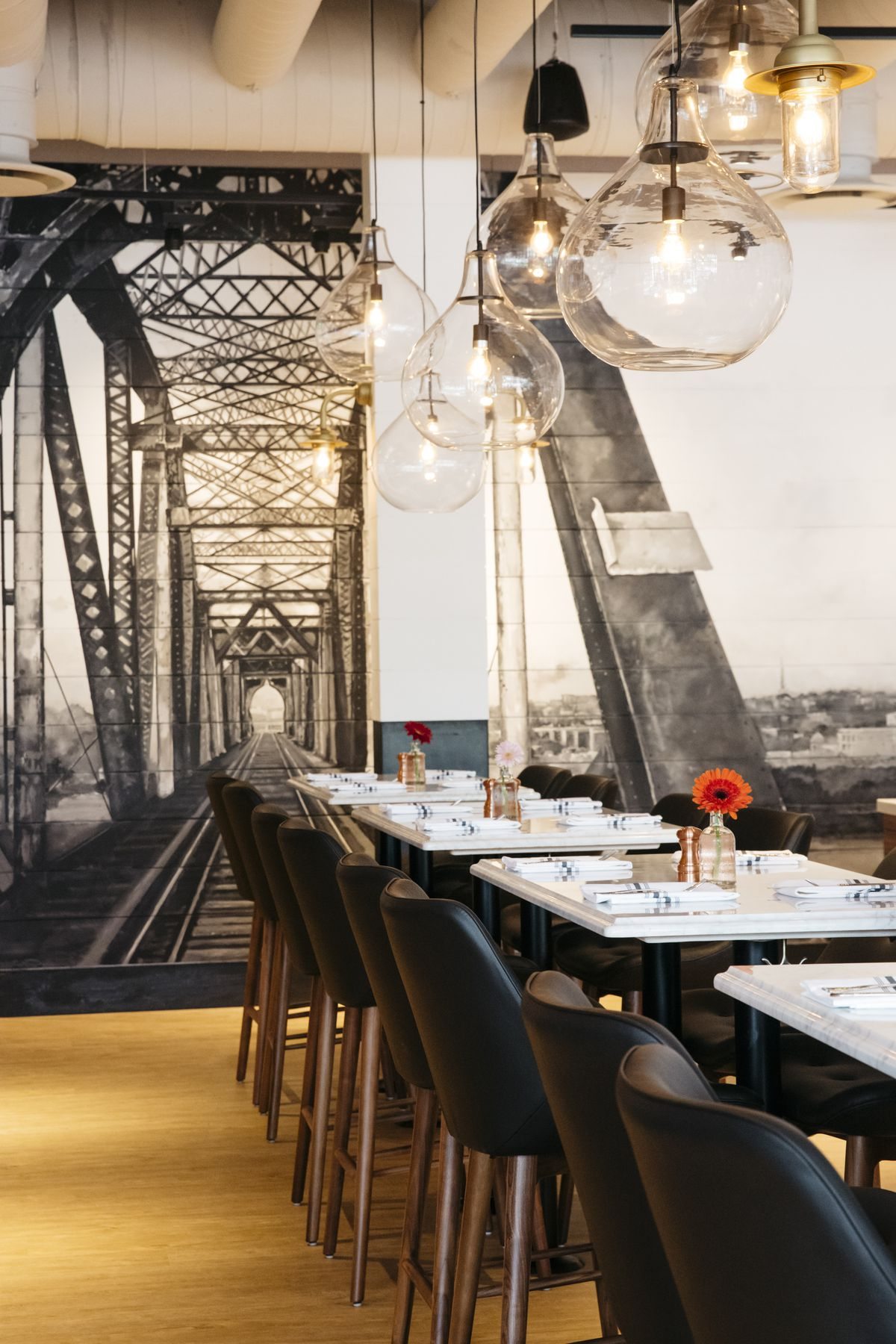 Bar height tables, black chairs, and a painted mural of Nashville's Cumberland Swing bridge