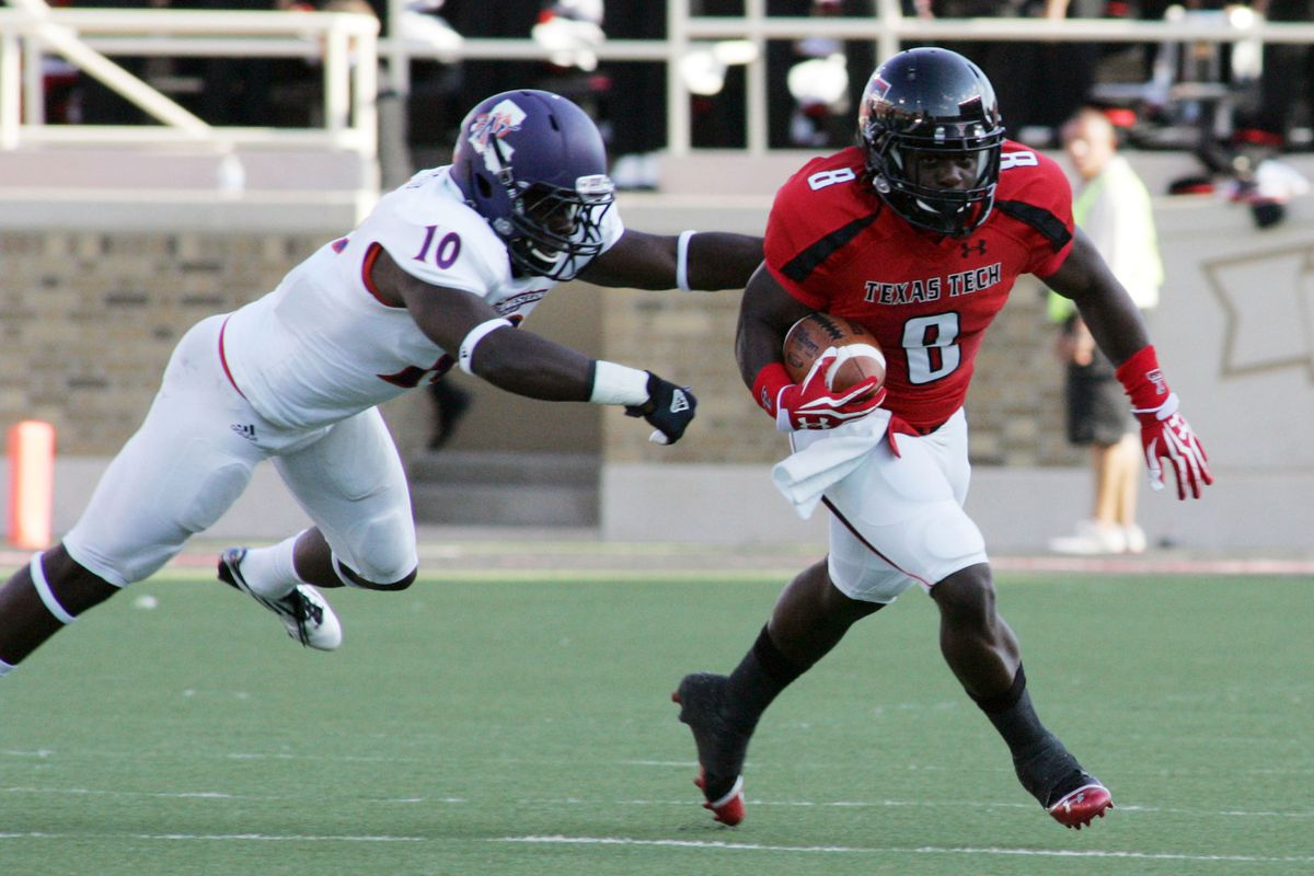 Sept 1, 2012; Lubbock, TX, USA; Texas Tech Red Raiders running back SaDale Foster (8) is chased  by Northwestern State Demons safety Bert White (10) during the first quarter at Jones AT&T Stadium. Mandatory Credit: Michael C. Johnson-US PRESSWIRE