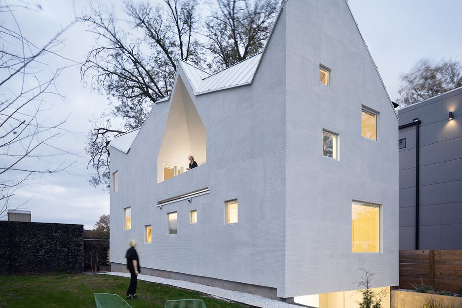 An angular white house with no front door and people walking around the side.
