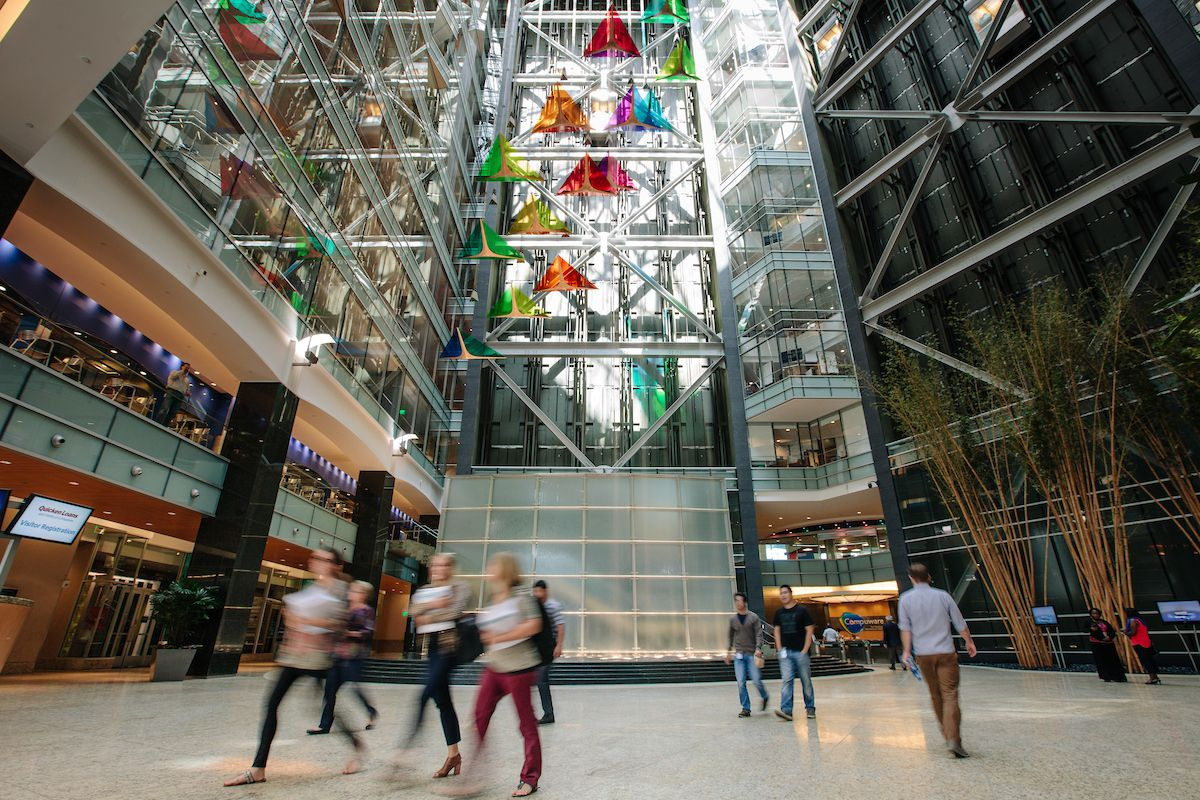 The interior of the Compuware World Headquarters in Detroit. The ceiling is high and glass and there are various colorful glass sculptures hanging.
