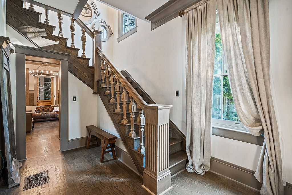 A staircase in a home with white walls and white drapes and porthole windows.