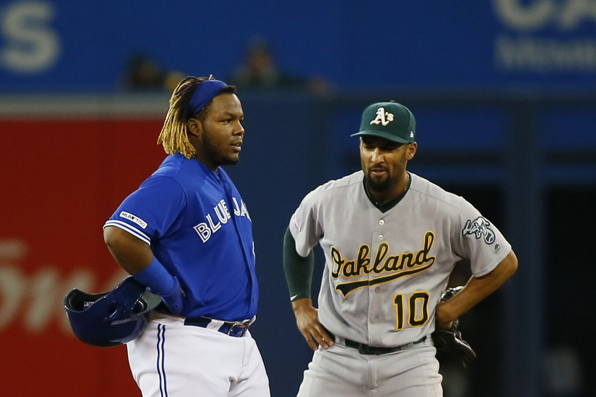 Toronto Blue Jays third baseman Vladimir Guerrero Jr. (27) talks with Oakland Athletics shortstop Marcus Semien (10) on second base during a stoppage in play in the second inning at Rogers Centre.