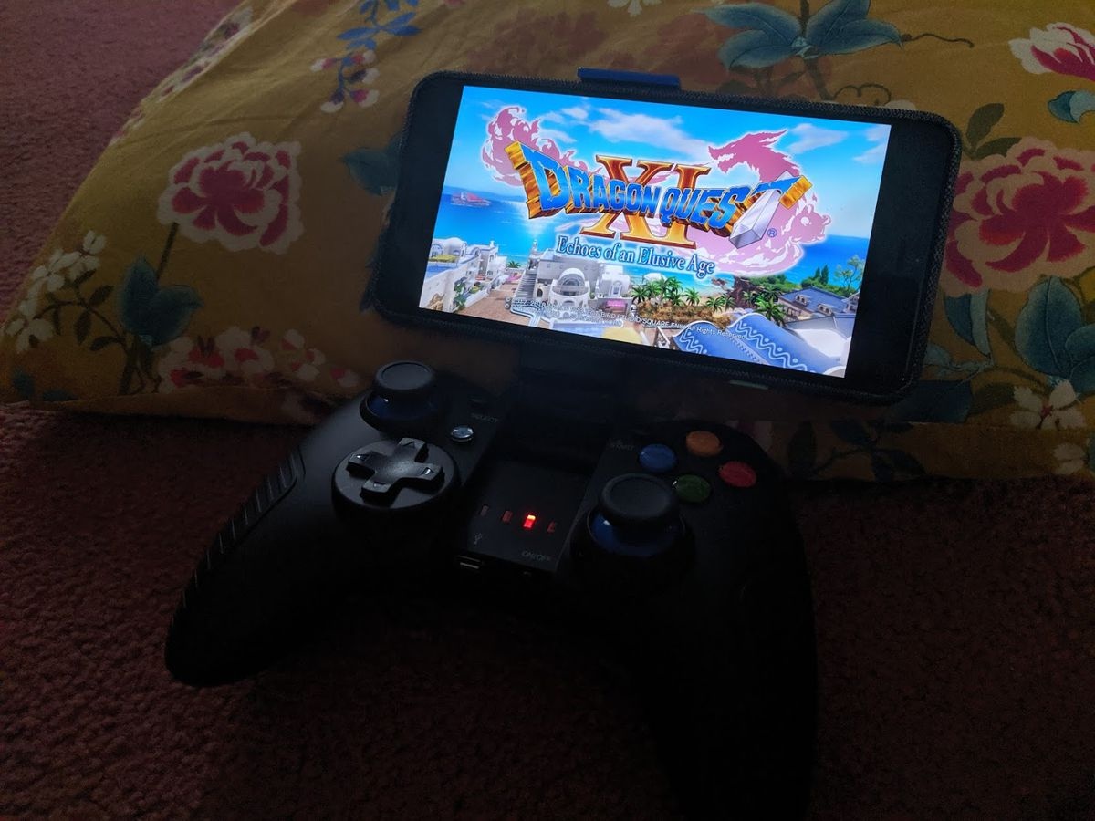 a photo of Dragon Quest 11: Echoes of an Elusive age being played on a smartphone that is sitting in a portable controller device