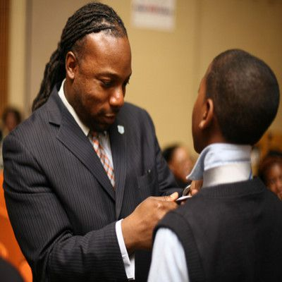 Man in suit and tie helps a younger man with his tie.