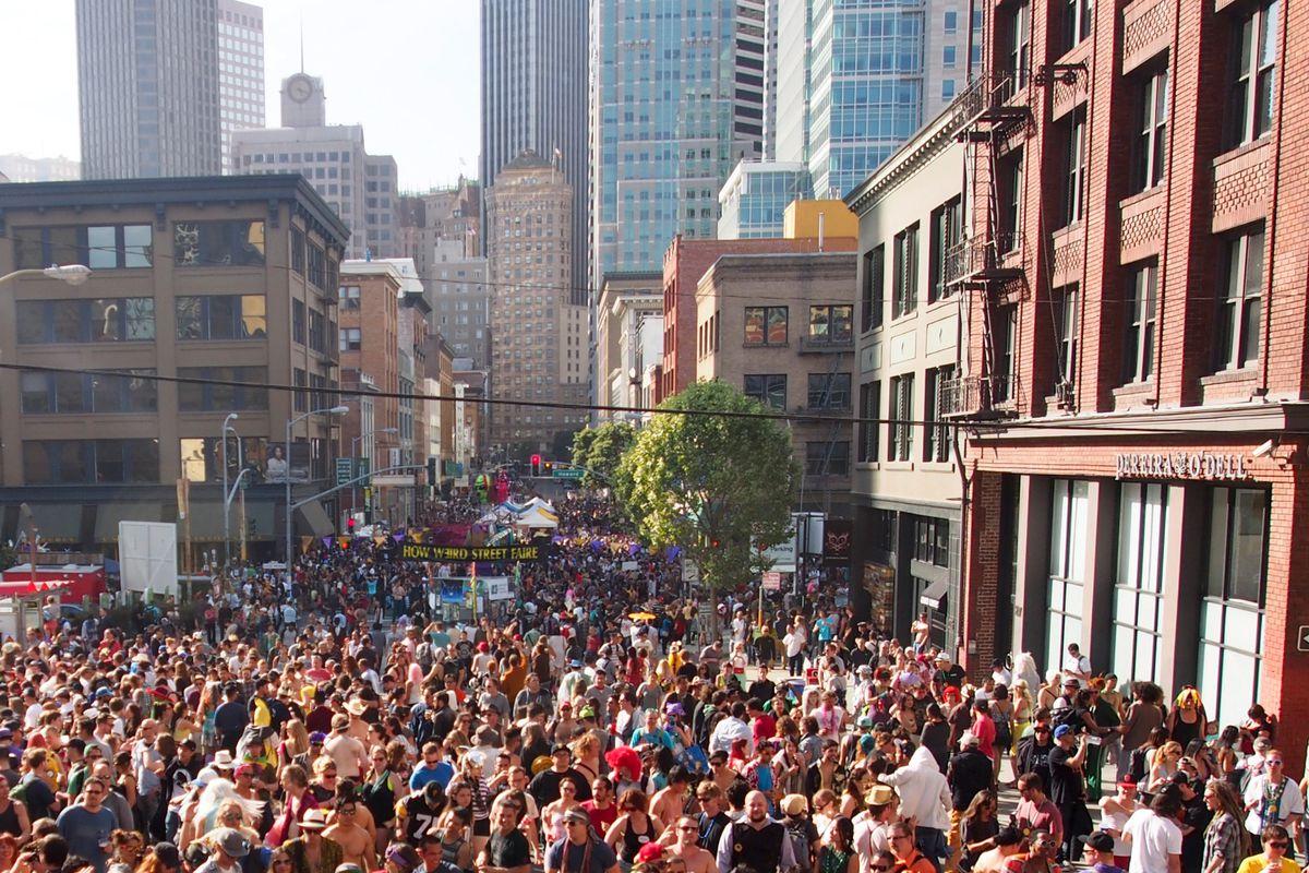 A huge crowd in a street fair.