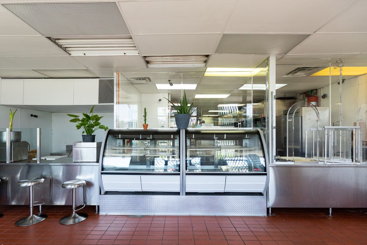 The carryout area at Pink Flamingo To-Go has red tiled floors and a counter made from metal with a deli case. Everything is surrounded by bullet-proof glass but there are also succulent plants that make it feel more welcoming.