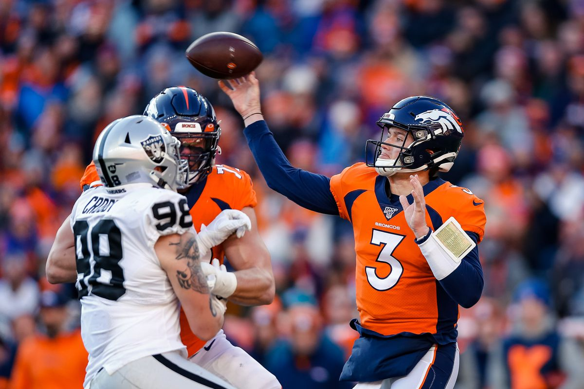 Denver Broncos quarterback Drew Lock attempts a pass as offensive tackle Garett Bolles defends against Oakland Raiders defensive end Maxx Crosby in the first quarter at Empower Field at Mile High.