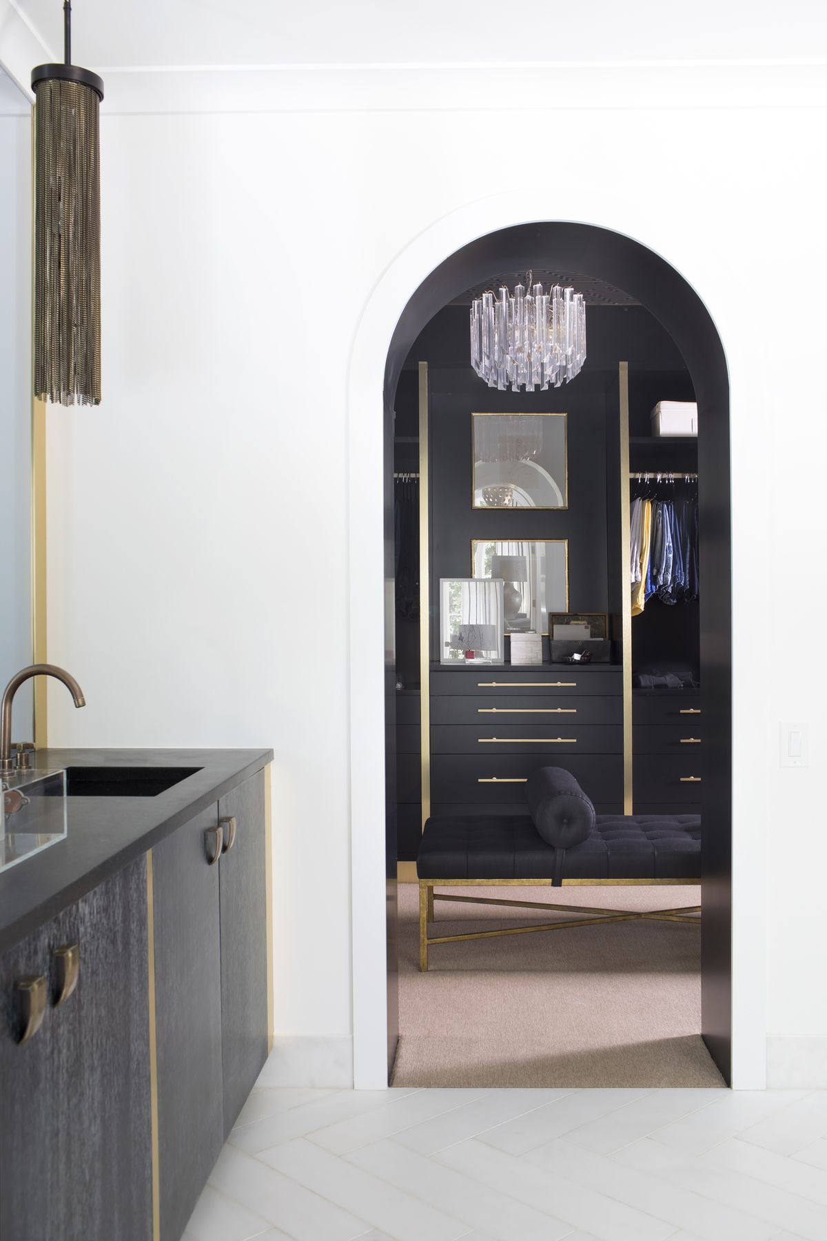 Between the master bathroom and closet, there is a lovely arched doorway. The bathroom is white, the closet is black.