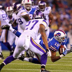 Aug 16, 2013; Orchard Park, NY, USA;  Minnesota Vikings defensive back Brandon Burton (27) watches as Buffalo Bills wide receiver DeMarco Sampson (19) makes a catch during the second half at Ralph Wilson Stadium.  Buffalo defeats Minnesota 20 to 16.