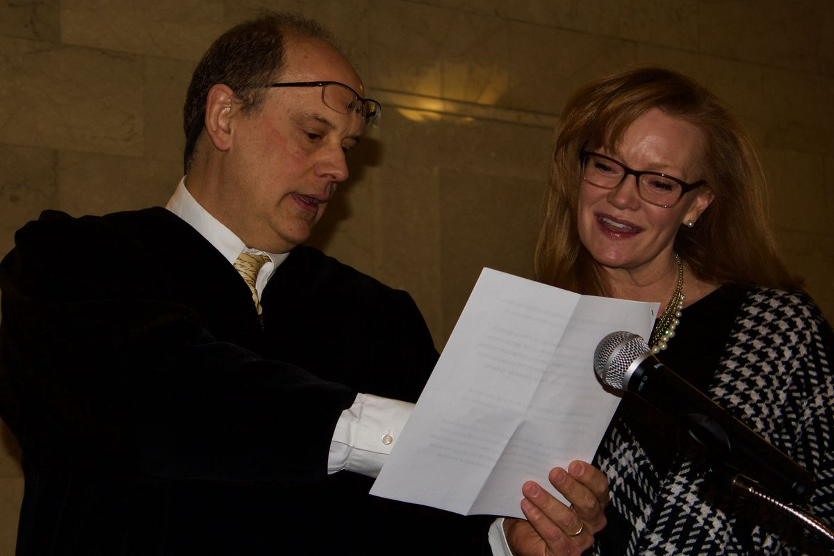 Rebecca McClellan, right, reviews the oath of office with appeals court Judge Dave Furman. McClellan, a Democrat, was later sworn in. Her victory in November shifted partisan control of the State Board of Education for the first time in nearly 50 years.