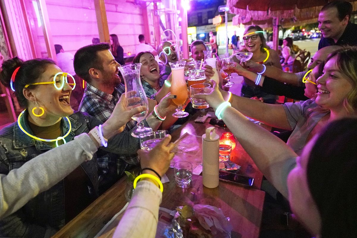 """Emily Baumgartner, left, and Luke Finley, second from left, join friends from their church group in a birthday toast to one of the members, upper right, during their weekly """"Monday Night Hang"""" gathering at the Tiki Bar on Manhattan's Upper West Side Monday, May 17, 2021, in New York."""