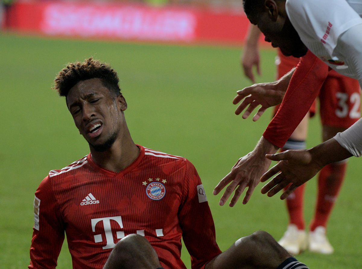 February 15, 2019, Bavaria, Augsburg: Football: Bundesliga, FC Augsburg - FC Bayern Munich, 22nd day in the WWK-Arena. Kingsley Coman from Munich sits on the lawn with a face distorted by pain. Shortly before the final whistle, he left the ground limping, injured his foot. The Bavarians won 2: 3.