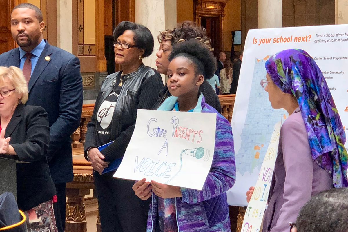 Students hold signs against a bill in the legislature that would allow a state takeover of the Gary and Muncie school districts.