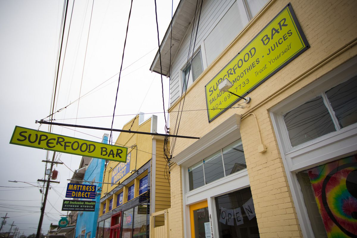 """The yellow brick exterior of a storefront with a bright green hanging sign that says """"Superfood Bar"""""""