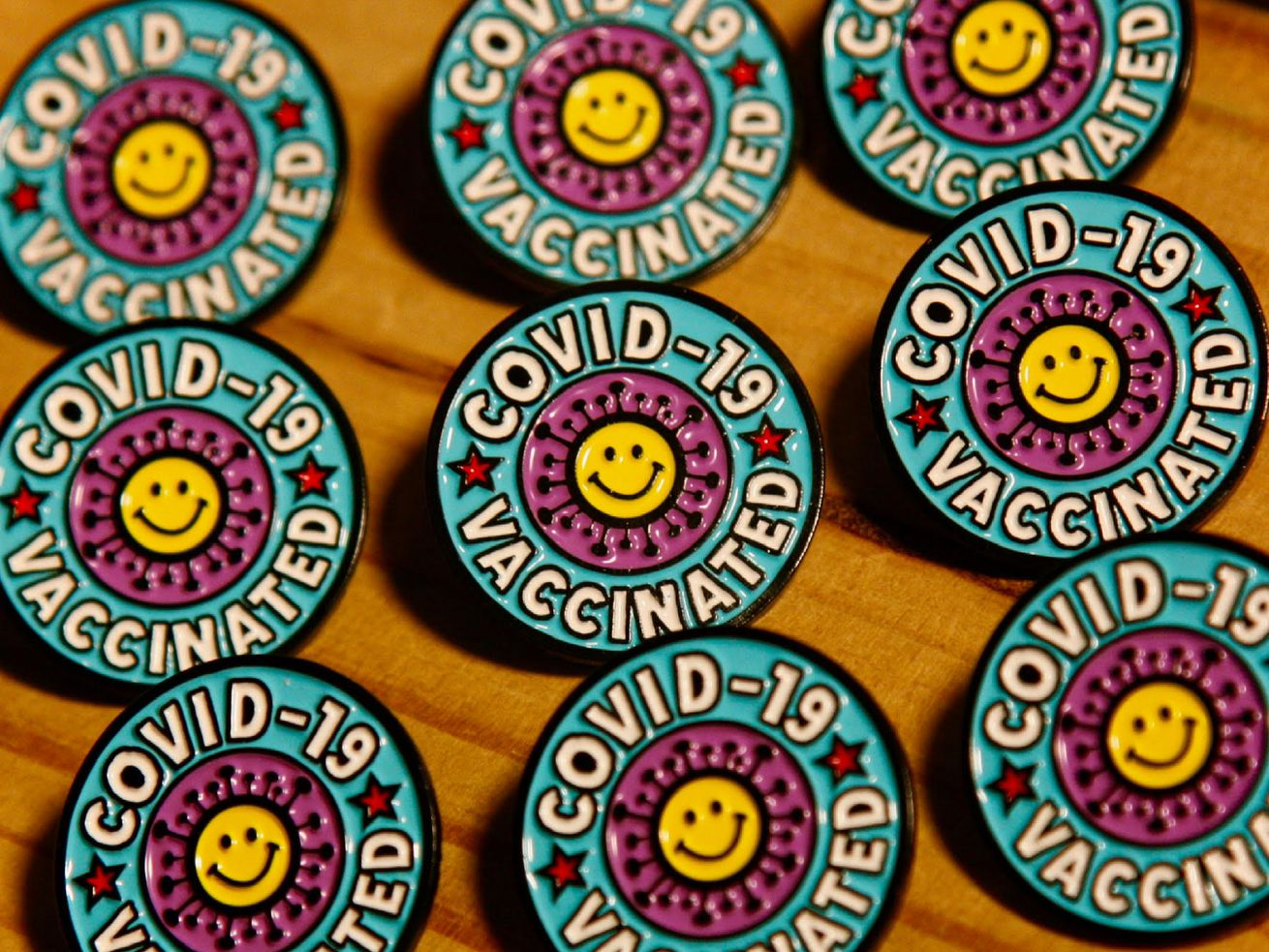 """Rows of illustrator Nate Duval's vaccine pin, which features a smiley face with spike protein and the phrase """"COVID-19 vaccinated."""""""