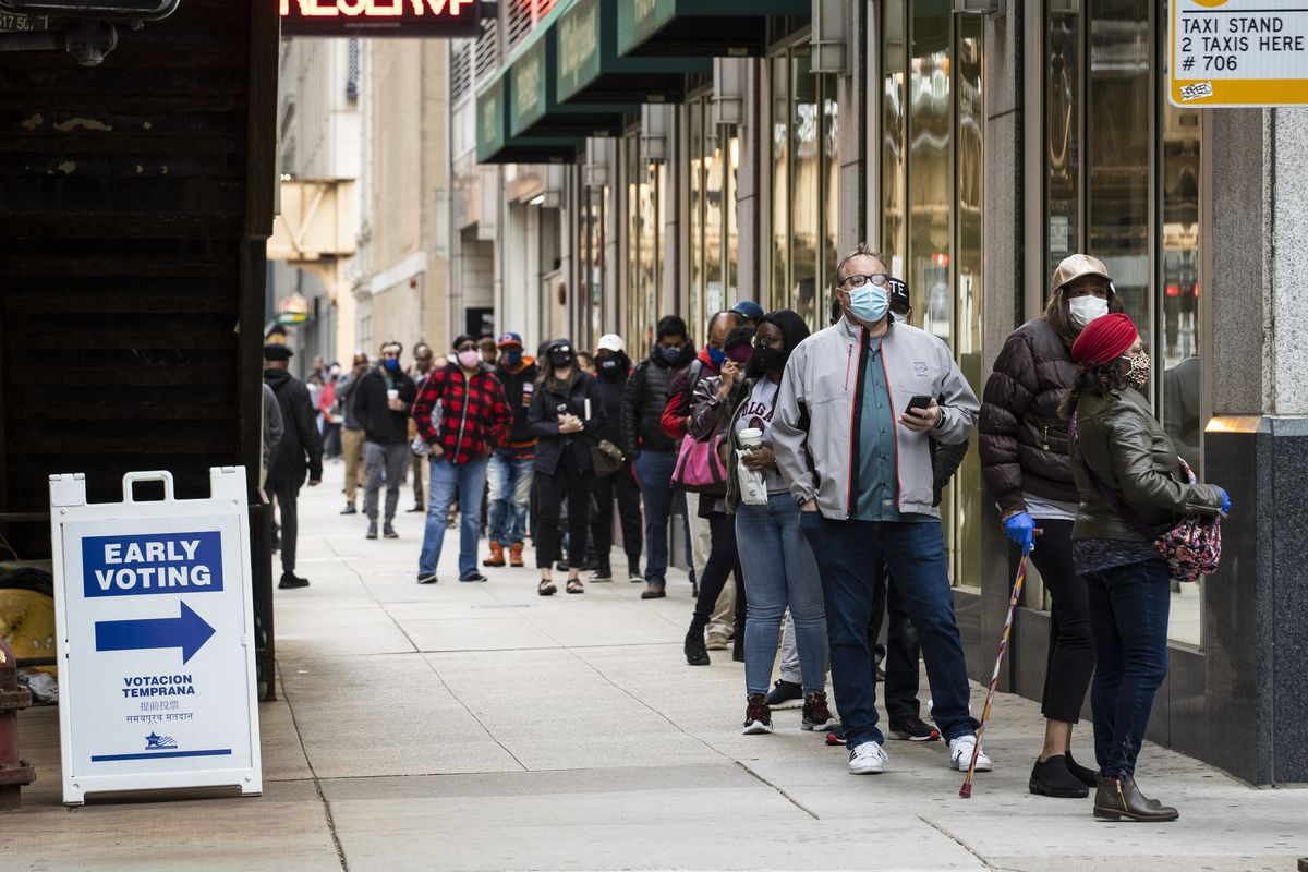People wait in line to early vote in downtown Chicago