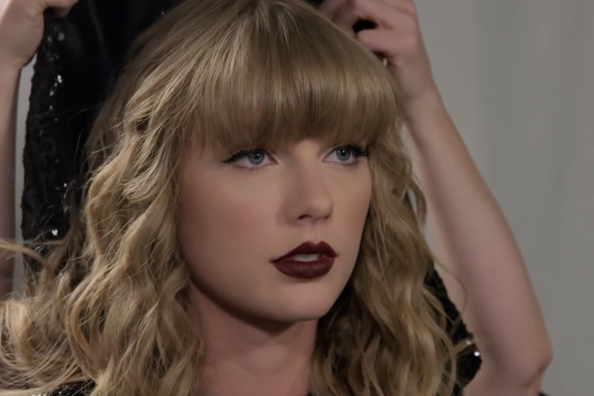 taylor swift, black sparkly hood removed, ready to go on stage, a fierce look on her face