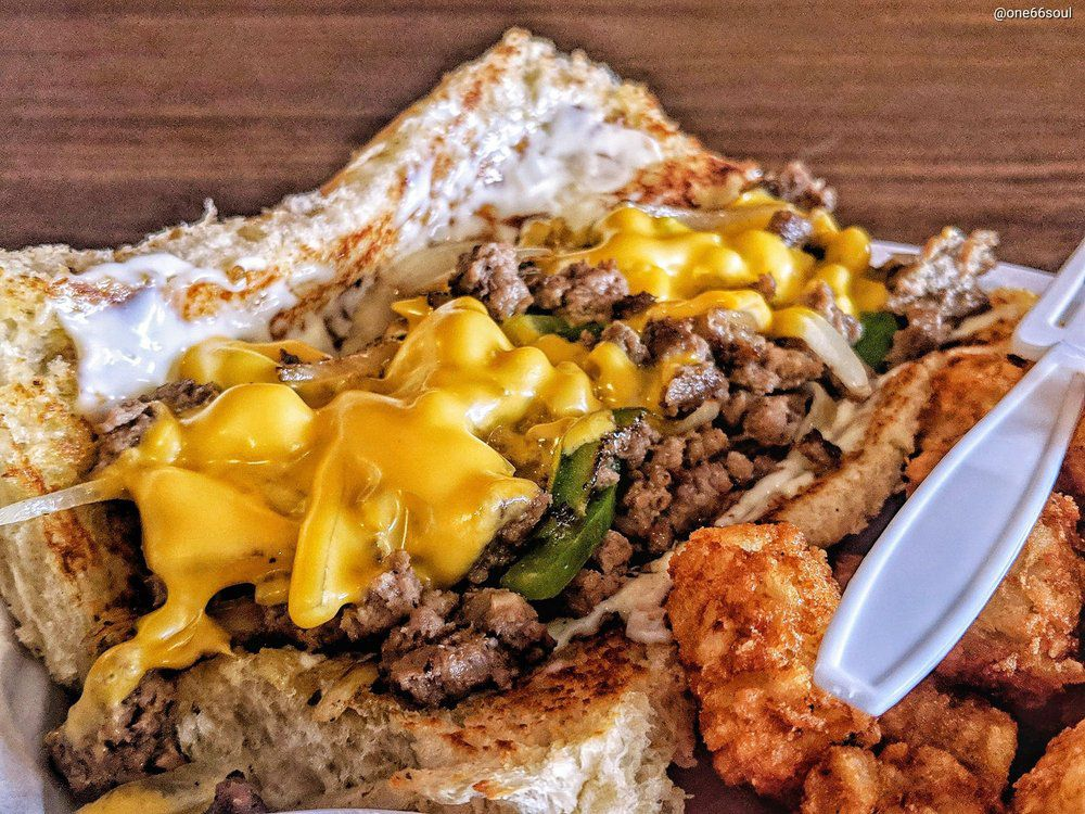 A close-up picture of a hot Chopped Cheese sandwich studded with peppers and topped with melting cheese alongside a helping of golden tater tots.