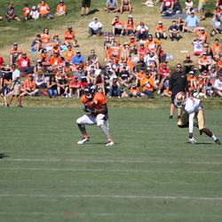 Broncos rookie WR Durron Neal pulls in a pass working against 49ers rookie CB Prince Charles Iworah.