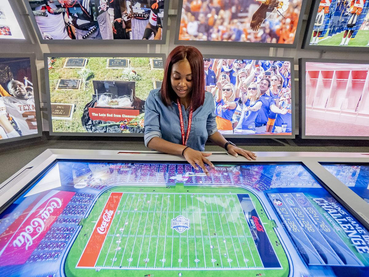 Girl using a touchscreen in an interactive exhibit that looks like a football field.