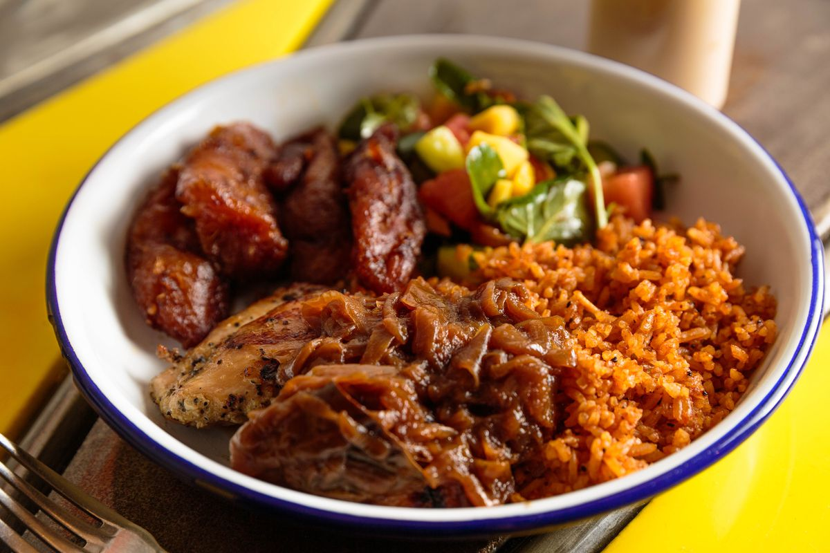 Onions drape over chicken yassa, which sits next to rice and plantains in a white bowl with a blue exterior