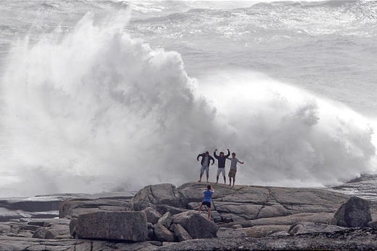 Wave watchers pose for photographs near Peggy's Cove, Nova Scotia, Sunday, as Hurricane Bill rakes the area.