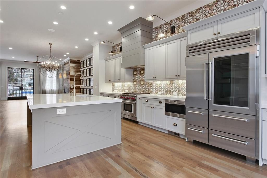 A huge kitchen with much tile and huge appliances.