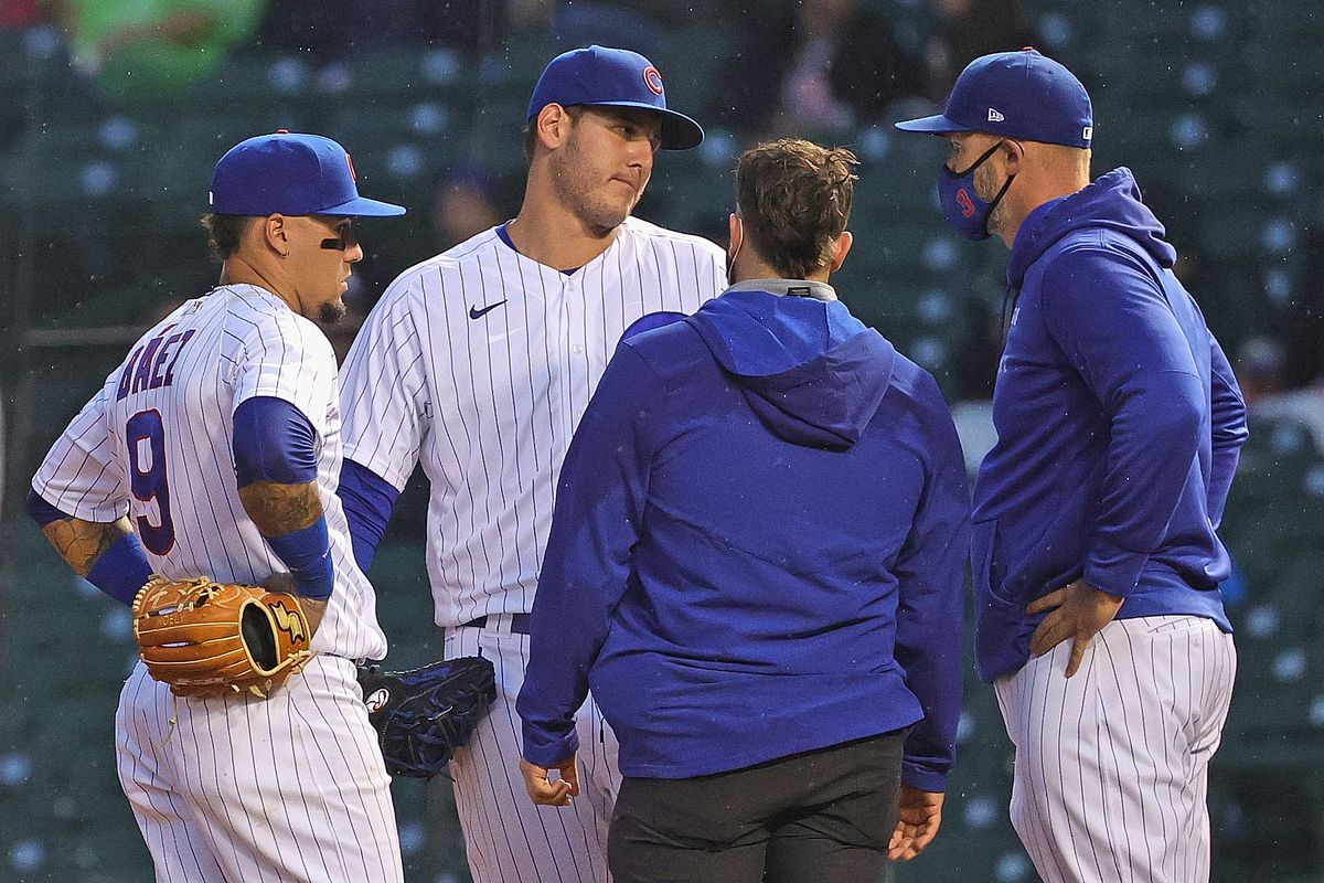 The Cubs' Anthony Rizzo talks with a trainer and manager David Ross as Javier Baez  listens before Rizzo leaves in the fifth inning of Tuesday's game against the Nationals at Wrigley Field.