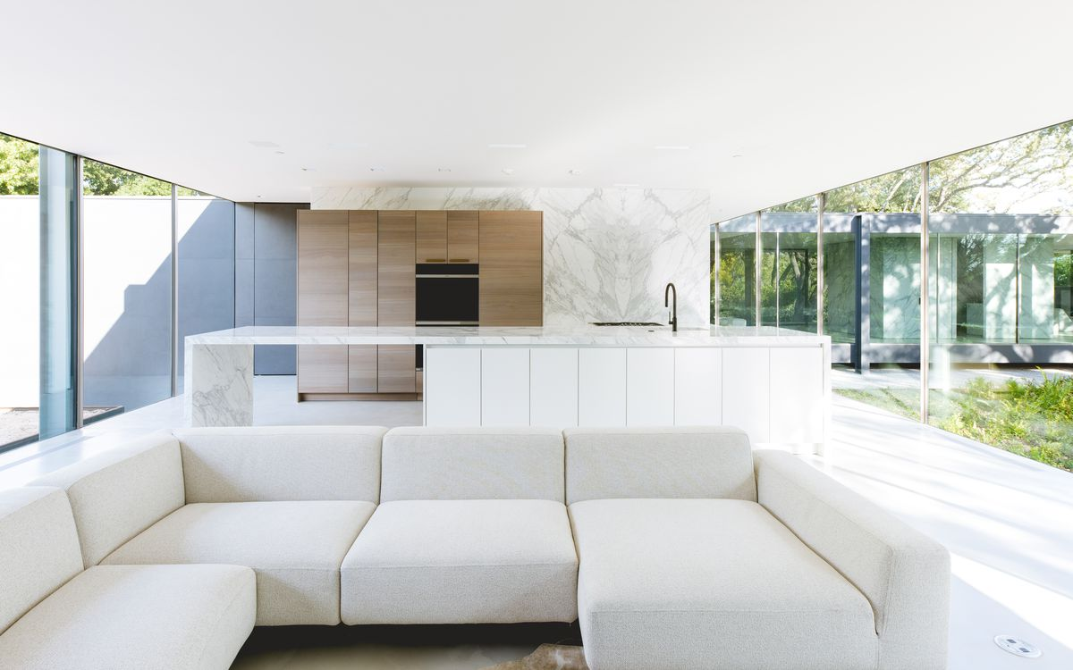 A white couch sits in a living room with a kitchen in the background. There are glass walls on both sides.
