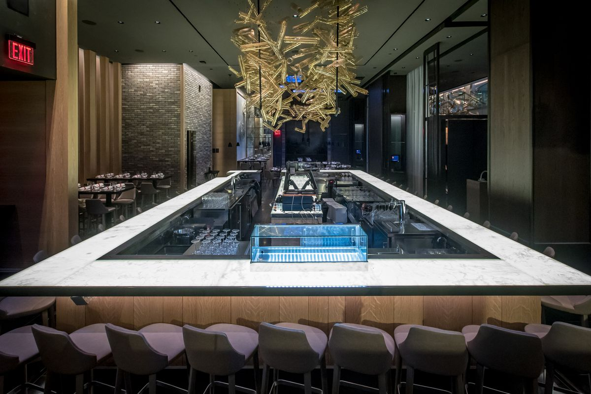A rectangular marble bar with with chairs all around it. Servers can stand inside on all four sides and serve guests across from it.