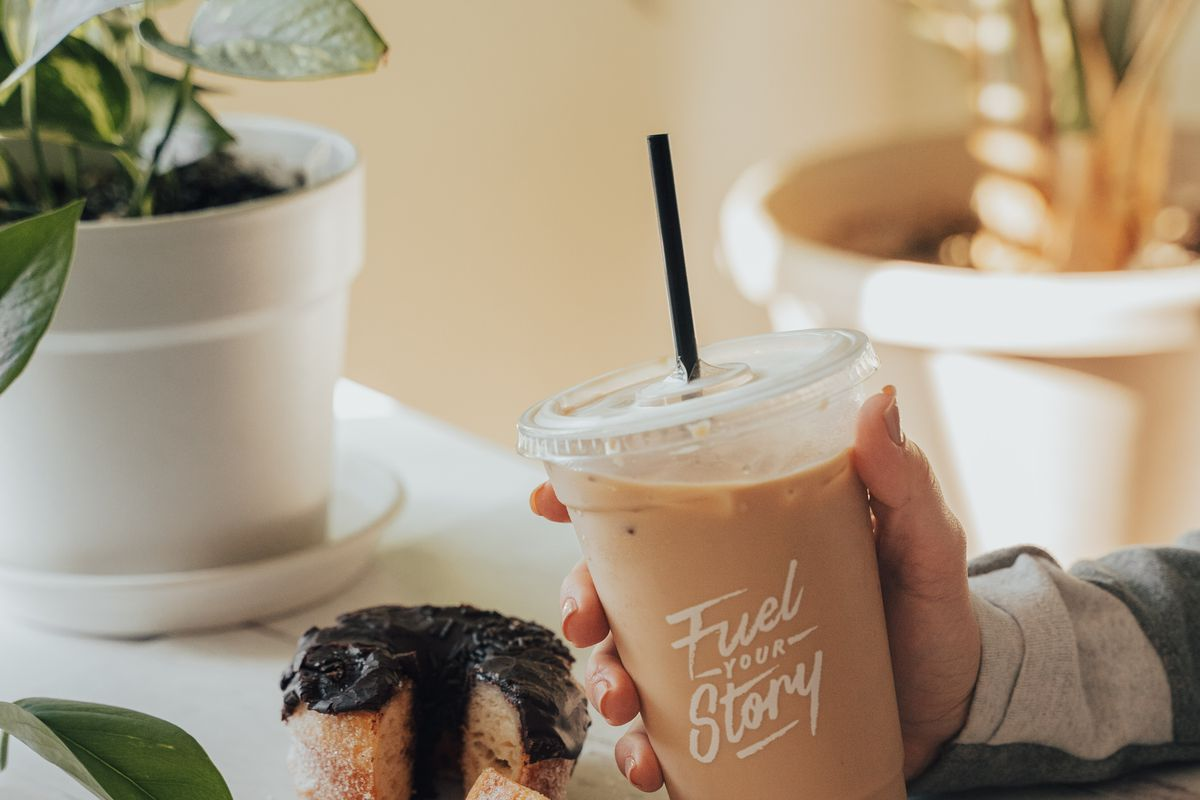 a person holding a latte in a to-go cup next to a backed sweet with chocolate icing