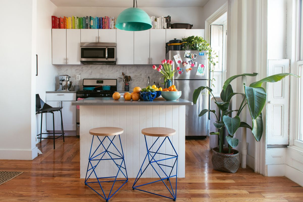 A kitchen with a kitchen island which is white with a blue countertop. There are two stools next to the kitchen island. On the island is a bowl of fruit, and colorful flowers in a vase. The walls are white and there is a blue light fixture hanging from th