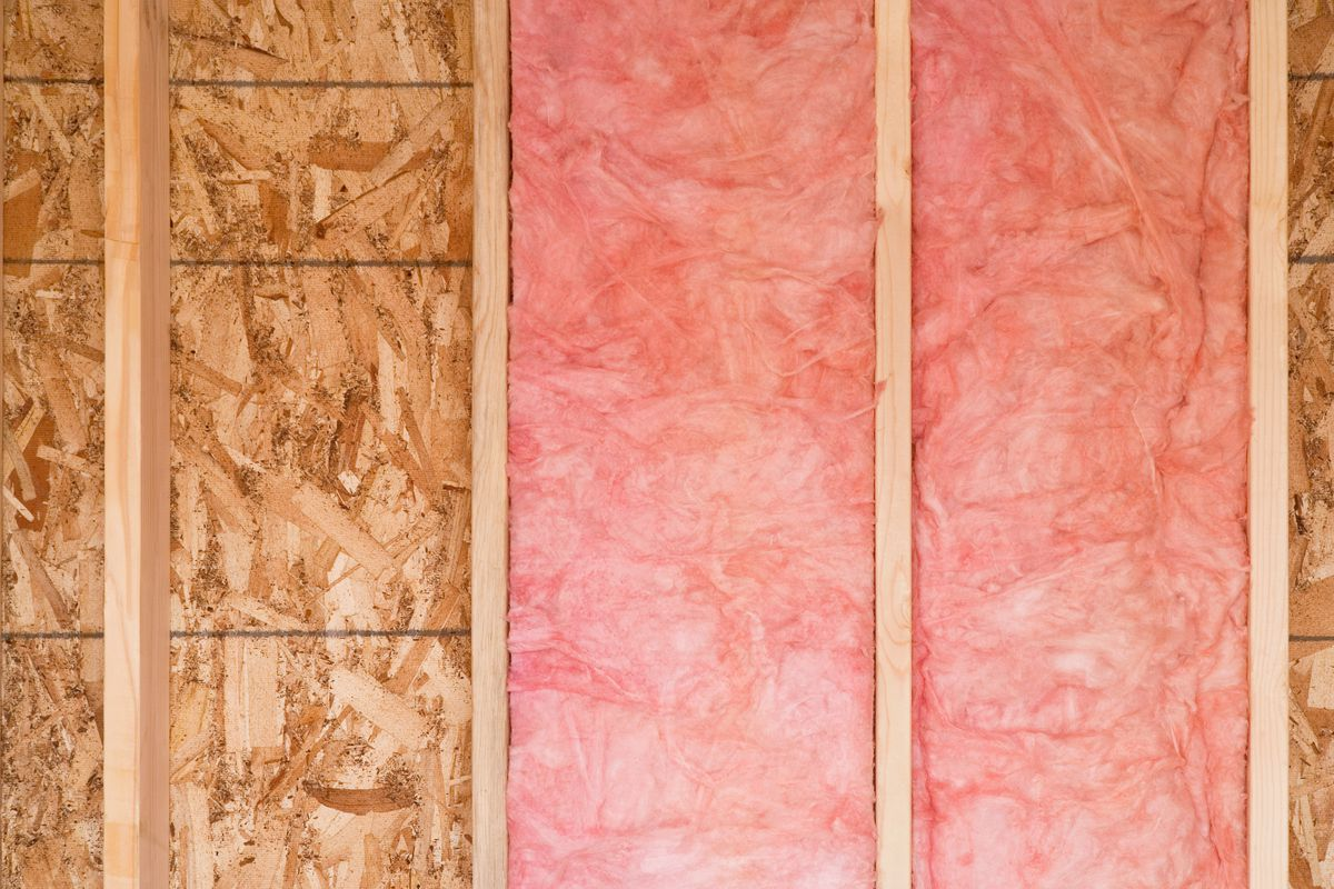 Close-up of strips of fiberglass insulation in a wall of a new home.