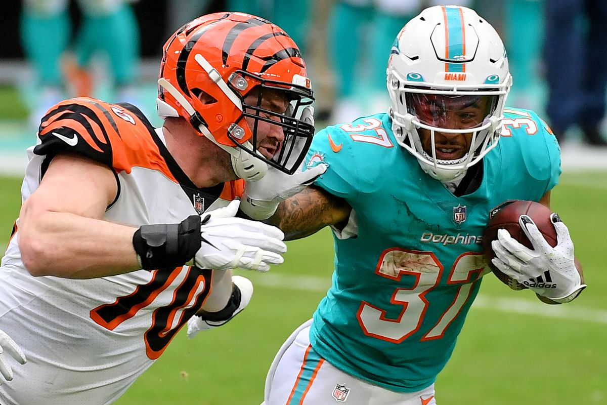 Miami Dolphins running back Myles Gaskin (37) stiff arms Cincinnati Bengals defensive end Margus Hunt (70) during the first half at Hard Rock Stadium.