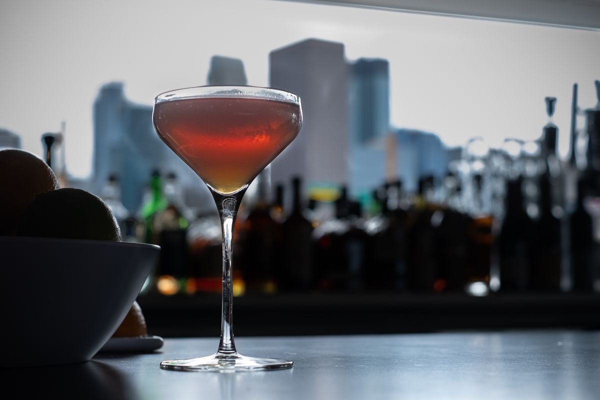 A coup with a Manhattan served up is placed on the bar with the Minneapolis skyline in the background