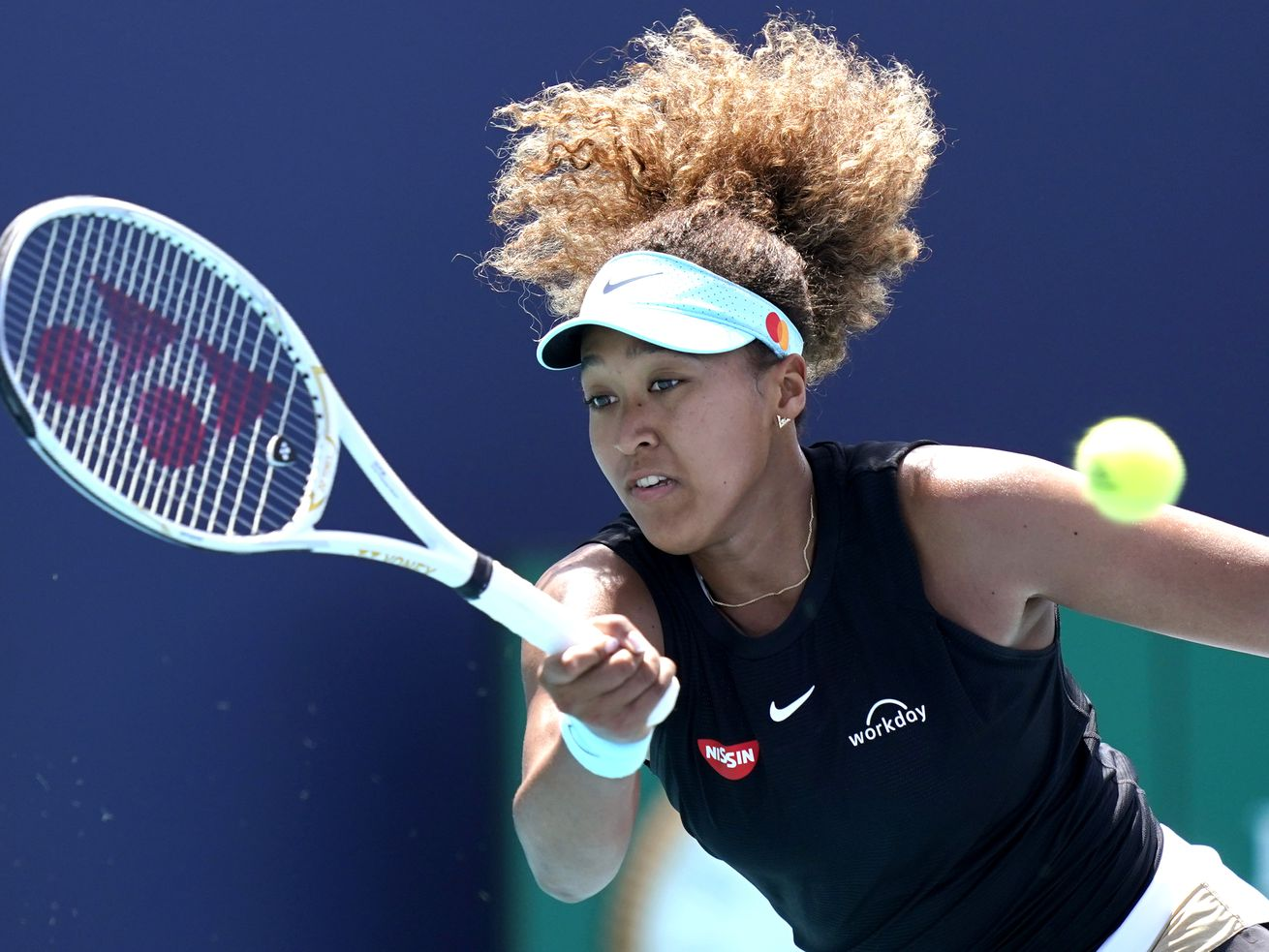 In this March 31, 2021 file photo, Naomi Osaka, of Japan, returns to Maria Sakkari, of Greece, during the quarterfinals of the Miami Open tennis tournament in Miami Gardens, Fla. Sponsors of Osaka are sticking by the her after she withdrew from the French Open citing mental health issues relating to the press conferences required for players. Osaka, a four-time Grand Slam champion, said Monday, May 31, she was withdrawing from the French Open for mental health issues.