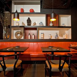 bold red leather couches contrast black tables and walls.